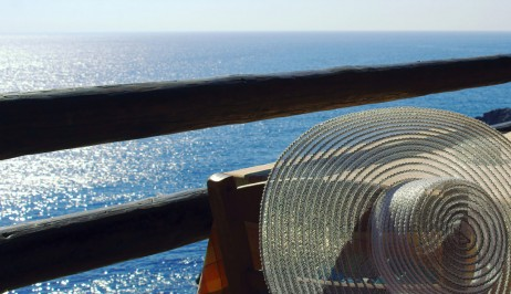 Straw hat on the back of the chair overlooking the sea at Dolphin Bay Family Resort Hotel in Syros