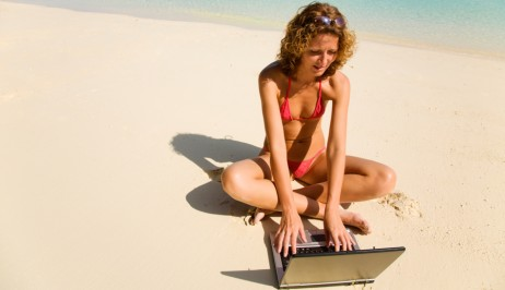 A lady uses her laptop on Galissas beach in Syros by the Dolphin Bay Family Resort Hotel.